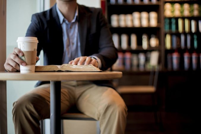 man-suit-coffee-shop-book-table-conversation